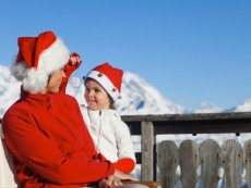 Mother and dauhter wearing Santa hats, playing